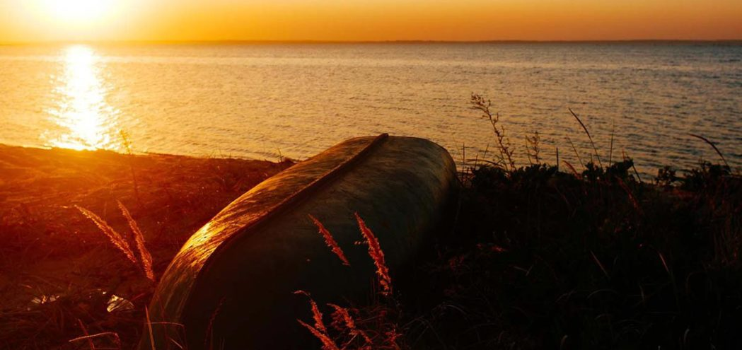Лодка лежит в траве на берегу моря
